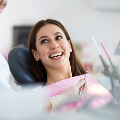 woman-smiling-in-dental-chair-for-exam