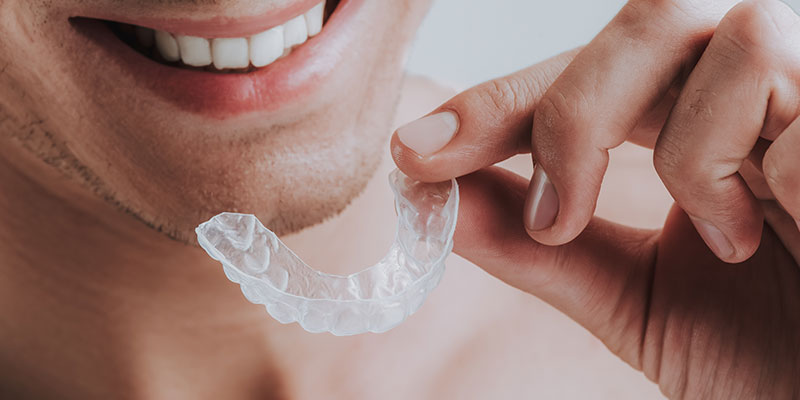 close-up-of-smiling-man-holding-transparent-mouth-guard