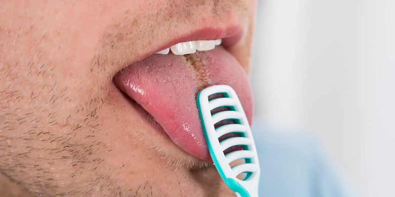 man-cleaning-his-tongue-to-avoid-bad-breath