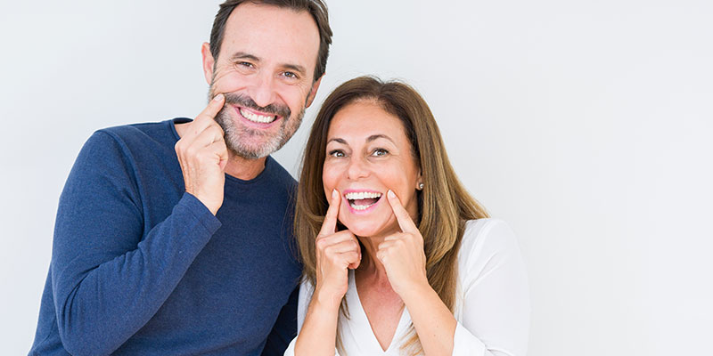 middle-aged-couple-smiling-and-pointing-at-their-teeth