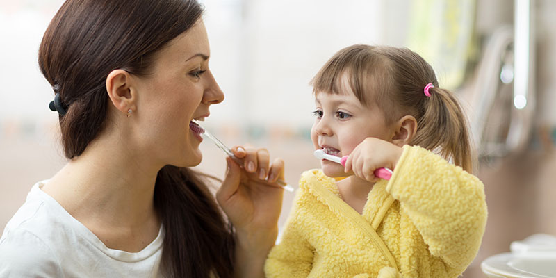 mother-teaching-daughter-how-to-brush-teeth-family-dentistry