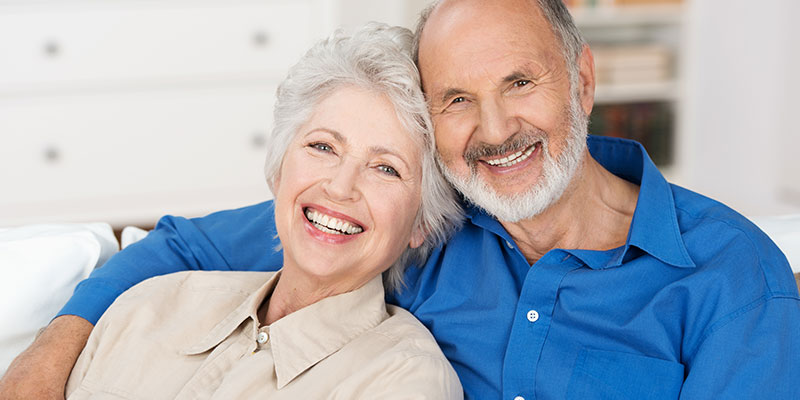 older-couple-smiling-in-living-room